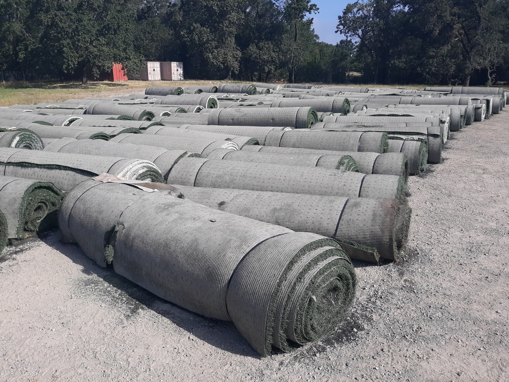 Rolls of old stadium turf that has been removed